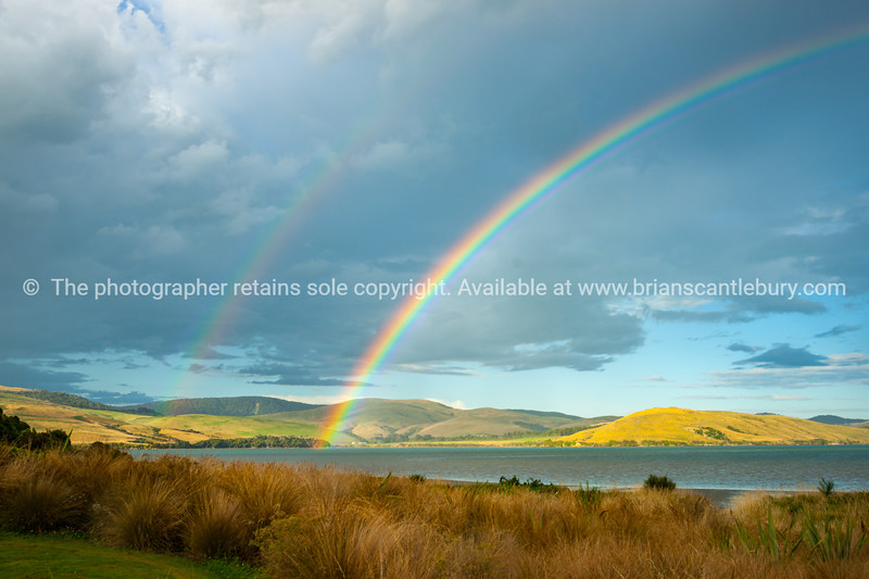 Sun strikes rolling farmland across the bay arched under rainbow under dark cloudy sky