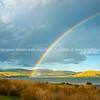 Sun strikes rolling farmland across the bay arched under rainbow under dark cloudy sky