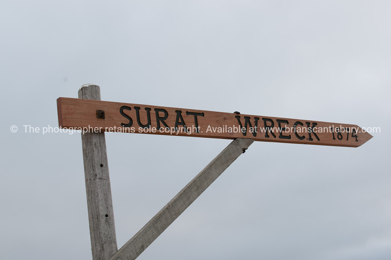 Rustic sign on Catlins beach pointing way to wreck of SSurat in 1874