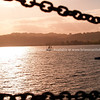 Yacht in evening light, framed by chain barricade on lake edge, Lake Taupo, New Zealand. New Zealand photographic stock images.