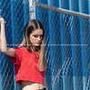 Looking bored, young woman in trendy clothes standing by industrial fence with blue  background.