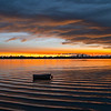 Gently blurred small boat rocking in bay at sunrise