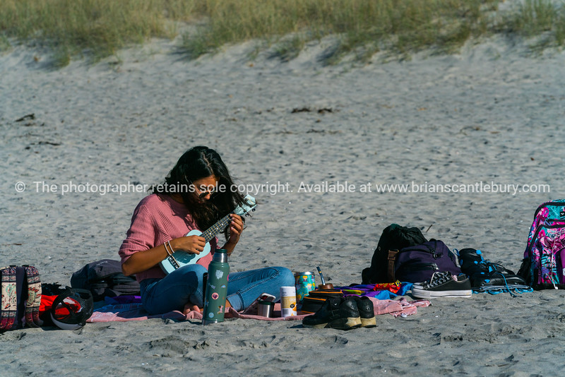 Woman sitting alone on beach playing ukulele surrounded by belongings. Releases; NO, please use for personal and editorial only.
