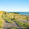 Track along fenceline past closed farm gate