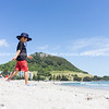 Boy in sun hat walks down Mount Maunganui beach.