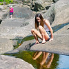 Attractive teenage girl sitting on rock by rock pool looking at reflection