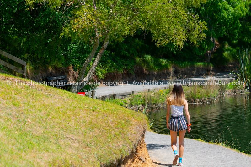 Teenage girl walking away along a path