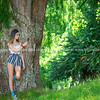 Teenager stands leaning against large tree in natural park