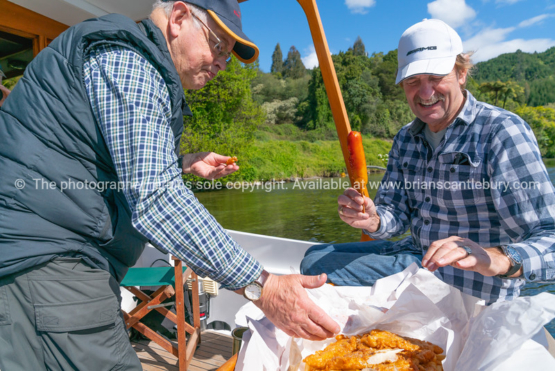 two mature aged men on back of boat on water tucking in to a feed of takeaway fish and chips in paper.
