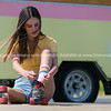 Pretty teenage girl sits on pavement changing shoes for retro old pair roller skates with red laces