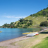 Pilot Bay at base of Mount Maunganui with active people paddling waka-ama on beautiful summers day.