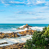Rough sea surges and splashes around North Rock of the rugged base of Mount Maunganui.