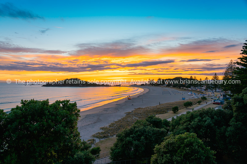 Intense colors of sun bursting over distant horizon viewed from slope of Mount Maunganui.
