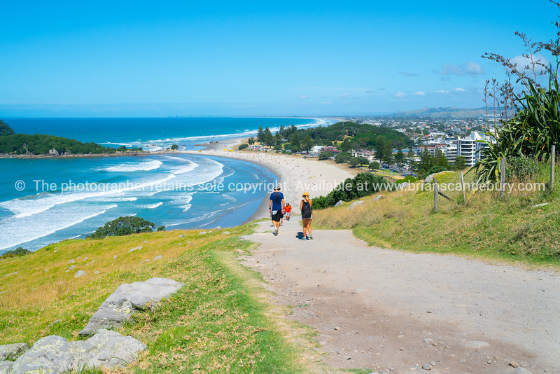 People walking on uphill track on Mount Maunganui with endless beaches stretching out to blue horizon