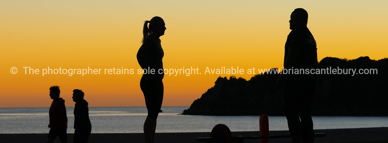 People on beach at Mount Maunganui at sunrise in silhouette doing morning fitnes exercise and walking by.