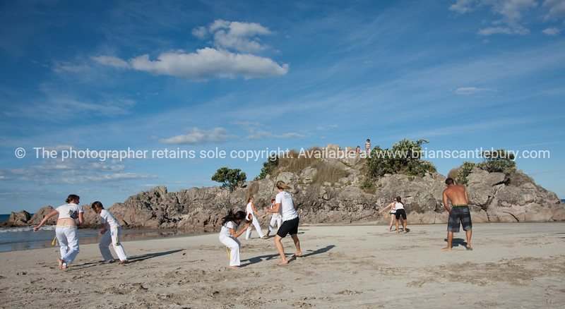 "Capoeira being practised on Mount Maunganui beach, Tauranga, New Zealand.<br /> Capoeira is a game, a sport, an art and a life philosophy, founded in Brasil in 1984. - 1<br /> Model Release; no. See;  <a href=""http://www.blurb.com/b/3811392-tauranga"">http://www.blurb.com/b/3811392-tauranga</a> mount maunganui landscape photography, Tauranga Photos; Tauranga photos, Photos of Tauranga Also see; <a href=""http://www.brianscantlebury.com/Events"">http://www.brianscantlebury.com/Events</a>"