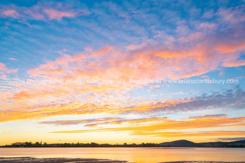 Brilliant sunset on harbor edge.