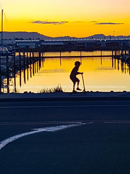 Boy on scotter passes marina on footpath in silhouette.
