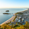 Mount Maunganui stretches out below as sun rises on horizon and falls across ocean beach and buildings