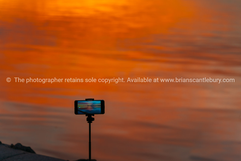 Mobile device on tripod standing by water's edge filming brilliant sunrise.