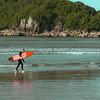 Vintage effect surfer leaving water carrying orange surfboard.