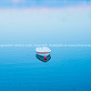 White dinghy afloat on calm blue water with reflection of sunset colors