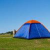 Blue tent with orange peak erected beside beach