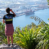 Young man on top Mount Maunganui with Port of Tauranga below.