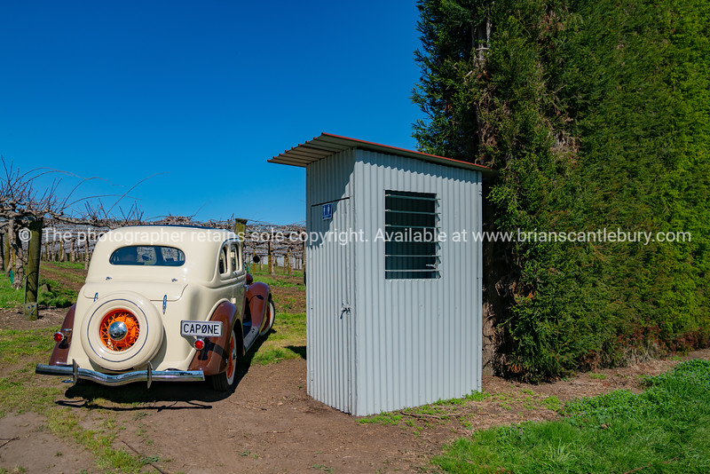 American classic car stopped in field outside workers toilet.