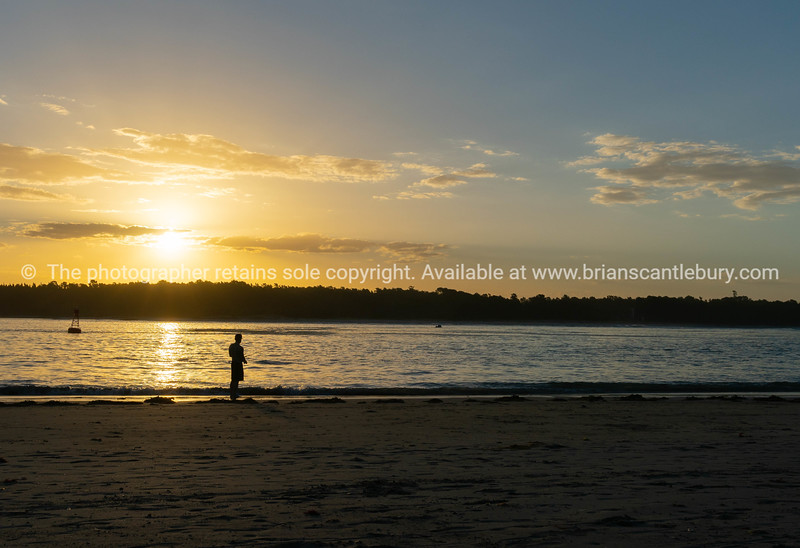 Distant silhouette of fisherman casting into Tauranga Harbour entrance,