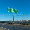 Road direction sign on Tauranga Harbour crossing bridge against blue sky