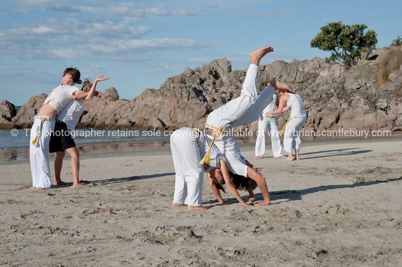 "Capoeira being practised on Mount Maunganui beach, Tauranga, New Zealand.<br /> Capoeira is a game, a sport, an art and a life philosophy, founded in Brasil in 1984. - 7<br /> Model Release; no. See;  <a href=""http://www.blurb.com/b/3811392-tauranga"">http://www.blurb.com/b/3811392-tauranga</a> mount maunganui landscape photography, Tauranga Photos; Tauranga photos, Photos of Tauranga Also see; <a href=""http://www.brianscantlebury.com/Events"">http://www.brianscantlebury.com/Events</a>"