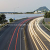Highway lightstreams along Takitimu Drive at dusk looking north with Mount Maunganui on horizon.