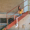 Attractive teenage girl contrasts with raw steel stairs behind building.