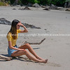 Teenage girl in yellow top and denim shorts sitting on piece of driftwood on beach