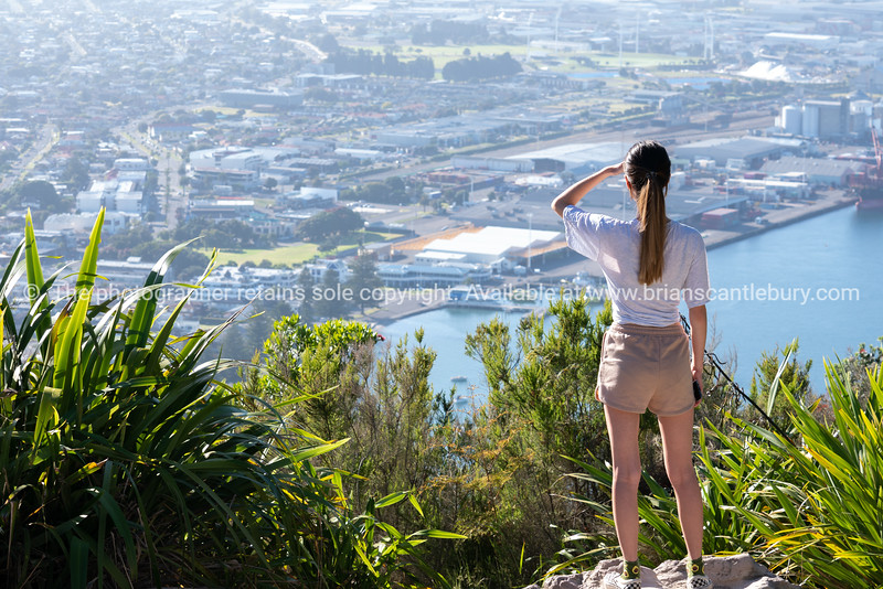 Teenage woman standing on summit of Mount Maunganui sheilding eyes and looking at view