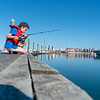 Boy sits on dock fishing
