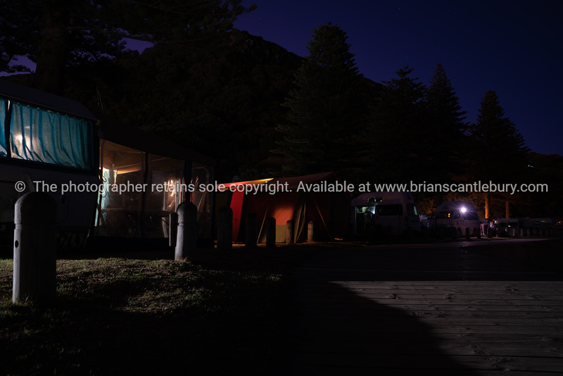 Row of holiday-making campers light through caravans an tents during night