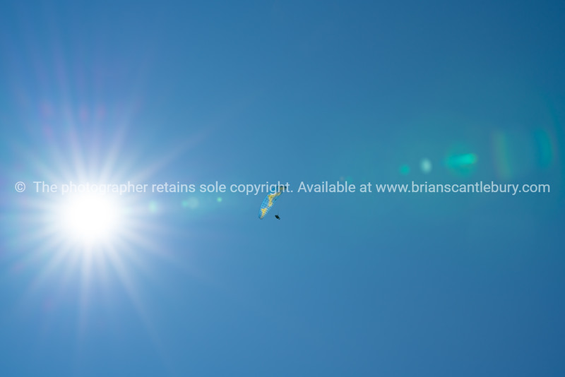 Bright sunburst and lenflare in sky with paraglider flying across.