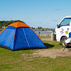 Blue tent with orange peak erected beside camper van near beach