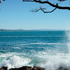 Ship arriving in entrance to Tauranga harbour passing rocky base of Mount Maunganui, New Zealand.