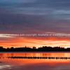 Vibrant sunrise across bay with flock of birds roosting on sandbar