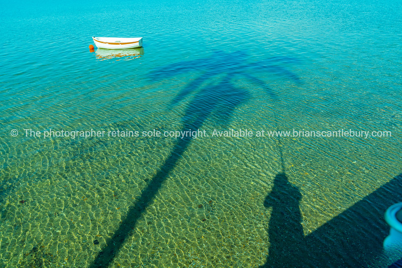 Idyllic coastal scene of calm shallow water with long diagonal palm tree shadow and small boat