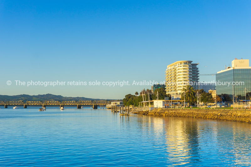 Tauranga waterfront and business district buidlings caught on golden glow of sunrise