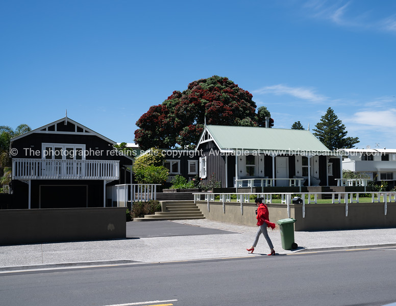 Woman in red top and shoes walks across footpath and past two quaint black cottages with green roof.