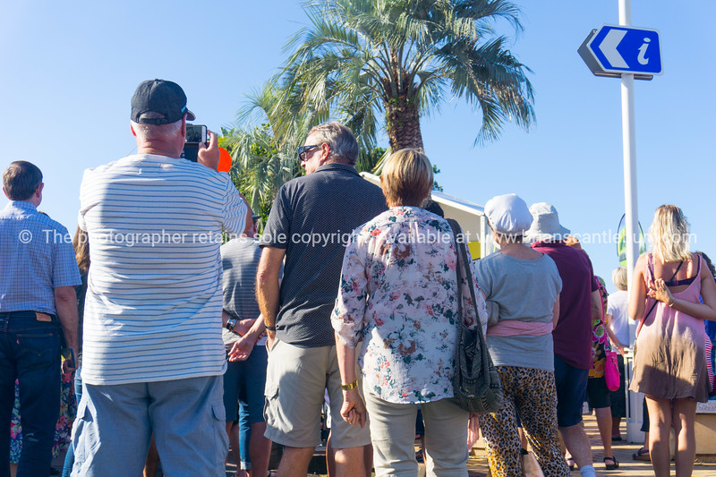 People enjoyiing  busy summer day  downtown watching band in National Jazz Festival, low point of view from behind.