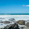 Whitewater from surf smoothed as it breaks around rugged coast at base of Mount Maunganui, New zealand