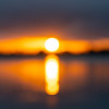 Intense golden sunrise intentionally defocused for abstract or background effect between layer of dark cloudy sky and sea