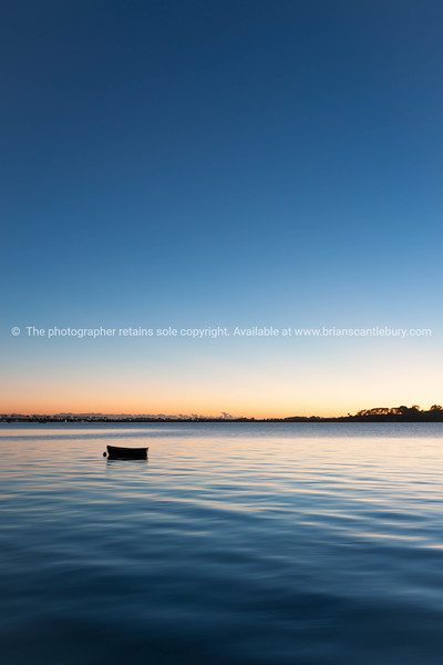 Sunrise across bay with small dinghy blue tones with orange around horizon