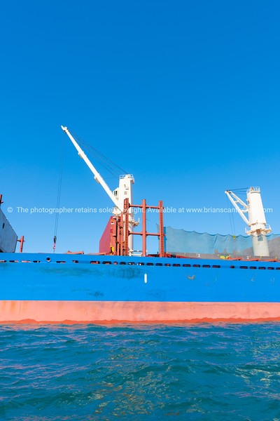 Blue and red hull of ship with white crane 1
